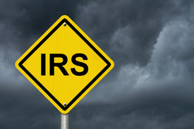 stock photo of irs  - IRS Warning Sign An American road warning sign with word IRS with a stormy sky background - JPG