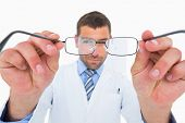 Smiling optician presenting eyeglasses on white background