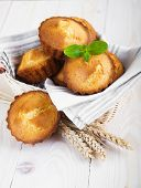 stock photo of bakeshop  - Homemade Muffins Ready for Breakfast in basket on a wooden background - JPG