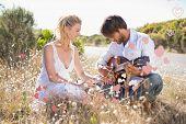 stock photo of serenade  - Handsome man serenading his girlfriend with guitar against valentines heart design - JPG