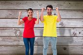 Excited couple cheering in red and yellow tshirts against digitally generated grey wooden planks