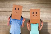Couple wearing emoticon face boxes on their heads against wooden surface with planks