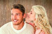 Attractive blonde whispering secret to boyfriend against wooden planks