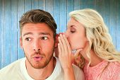 Attractive blonde whispering secret to boyfriend against wooden planks