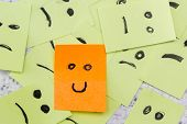 pic of perception  - concept for a positive attitude with small office notes with multiple faces and one that stands out with a smile - JPG