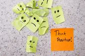 stock photo of positive  - concept for a positive attitude with small crumbled up sad faces and a note with the phrase think positive - JPG