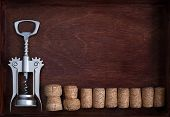 Corkscrew And A Row Of Wine Corks Into Dark Box