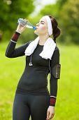 Caucasian Sportive Woman Drinking Water During Her Regular Joggong Workout Outdoors.