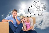 Unhappy young couple sitting beside moving boxes against blue sky with clouds and sun