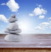 Rocks balancing on table in front of blue sky