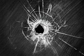 stock photo of car-window  - Bullet shot cracked hole on car windshield or accident damaged broken house window glass  - JPG