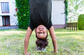 African girl playing on meadow in front of home doing handstand