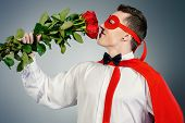 Young handsome man in a superhero costume holding a bouquet of red roses. Love concept.