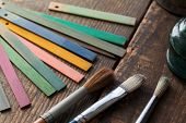 picture of bristle brush  - Wood color samples and brushes on an old wooden surface - JPG