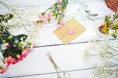 Love note in small envelope surrounded by pink carnations on wooden table