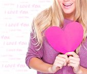 Closeup photo of body part of cute blond woman holding in hands pink paper heart, romantic feelings, happy Valentine day decoration