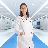 Serious female doctor standing at a hospital corridor