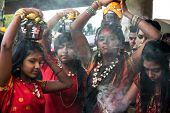 KUALA LUMPUR, MALAYSIA - FEBRUARY 3, 2015: Hindu devotees carry milk pots on their heads walk in a procession to the Batu Caves temple on Thaipusam day, a day of thanksgiving and devotion.