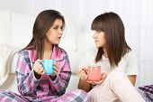 picture of pajamas  - Beautiful girls twins in pajamas drinking tea at home - JPG