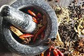 picture of garam masala  - Granite mortar and pestle with spices ready for grinding - JPG