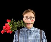 Geeky hipster biting a bunch of roses against black