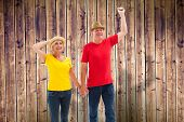 Mature couple walking and holding hands against wooden planks background