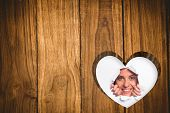 Young woman looking through paper rip against heart in wood