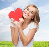 happiness, health, people, holidays and love concept - smiling young woman in white t-shirt holding red heart over blue sky and grass background