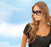 people, fashion, elegance and style concept - beautiful young woman in shades over blue sky and cloud background