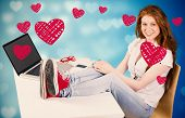 Pretty redhead with feet up on desk against valentines heart design