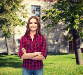 happiness and people concept - smiling young woman in casual clothes with crossed arms