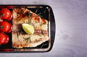 stock photo of pangasius  - Dish of Pangasius fillet with rosemary and lime on metal tray and color wooden table background - JPG