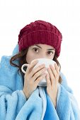 picture of shivering  - Woman shivering and warming herself under a blanket and drinking hot tea - JPG