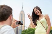 NYC asian chinese tourist girl posing at Empire State Building doing the v hand sign. Young couple of tourists taking pictures with smartphone in New York City in front of famous landmark building.