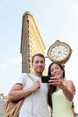 New York couple taking tourist selfie Flatiron NYC. Young adults taking a picture with smartphone in front of attraction building in NYC in summer.