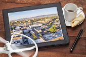 drone aerial photography concept - reviewing aerial pictures of Fort Collins downtown on a digital tablet with a drone rotor and cup of coffee