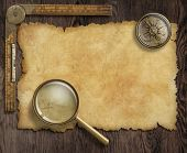 stock photo of treasure map  - vintage nautical compass and loupe on table with treasure map - JPG