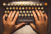 pic of qwerty  - Color horizontal detail of two hands typing on the keyboard of an old typewriter - JPG
