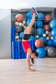 handstand woman workout at gym with swiss balls background