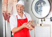 Portrait of confident male butcher holding meat in butchery