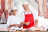 Portrait of confident male and female butchers working at counter in butchery