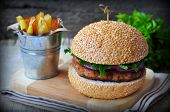 image of burger  - Closeup of home made burgers with the fried potato on wooden and linen background - JPG