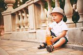 Little Boy In Hat Sitting Near Balustrade