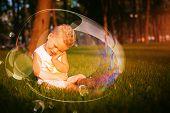 Little Shy Boy Sitting In Grass