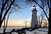 image of marblehead  - The historic Marblehead Lighthouse in Northwest Ohio sits along the rocky shores of the frozen Lake Erie - JPG