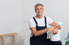 stock photo of overhauling  - Portrait Of Happy Mature Painter With Stepladder And Paint Bucket - JPG