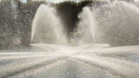 image of gushing  - High pressured water gushing out of a pipes creating a beautiful water fountain - JPG