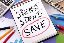 pic of calculator  - The word Save circled in red below a list of spending written on a notepad surrounded by pencils graphs books and calculator - JPG