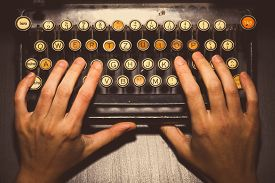 image of qwerty  - Color horizontal detail of two hands typing on the keyboard of an old typewriter - JPG