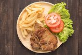 stock photo of pork chop  - grilled pork chop steak and vegetables with french fries on wooden background - JPG